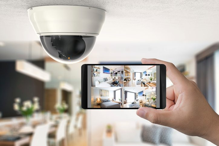 Gill Insurance | hand holding 3d rendering mobile connect with security camera